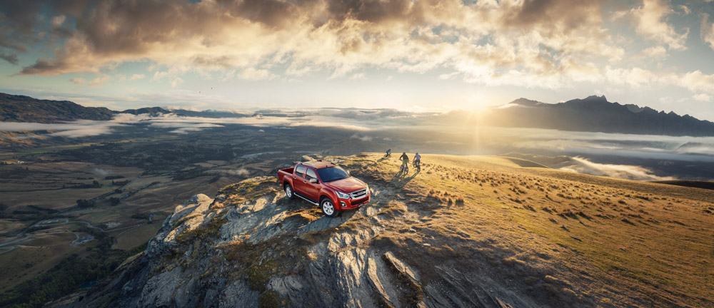 16MY-15B-ISUZU_D-MAX_Top_of_the_mountain_Front_with_talent_EU_LHD